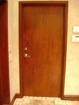 A metal door wood-grained like mahogony