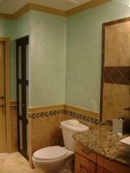 Soft green walls accent the travertine tiles