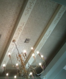 Ceiling beam design complements stencil wallpaper on this grand room ceiling